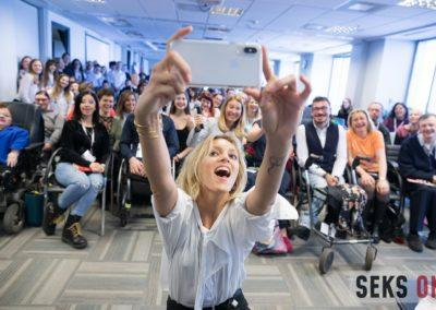 Anja Rubik robiąca selfie zuczestnikami konferencji. Wszyscy uśmiechnięci.