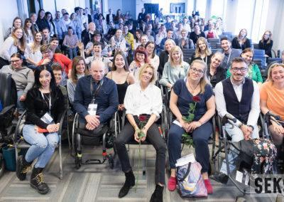 Uczestnicy konferencji pozują dozdjęcia zgromadzeni wdużym pomieszczeniu. Grupa zróżnicowana wiekowo. Są wniej ikobiety, imężczyźni. Część znich zniepełnosprawnością. Wszyscy się uśmiechają. Wprawym dolnym rogu fotografii logotyp projektu Sekson.