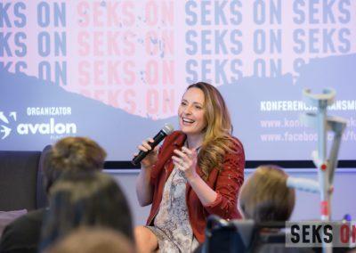 Monika Kuszyńska podczas prelekcji, mówi domikrofonu, gestykuluje.