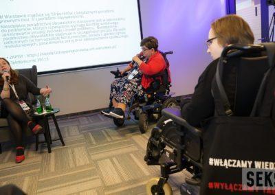 Anna Thieme siedząca nafotelu, obok Beata Świniarska nawózku. Kobiety są wtrakcie prelekcji, zanimi prezentacja. .
