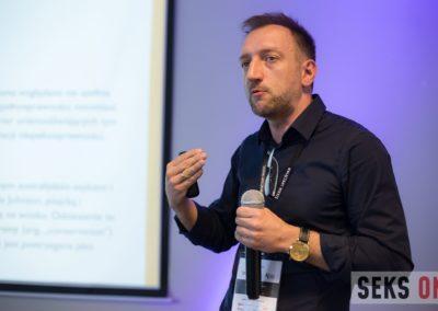 Remigiusz Kijak gestykuluje podczas wykładu, wtle prezentacja.