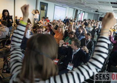 Ćwiczenia podczas przerwy wtrakcie konferencji, uczestnicy podnoszą ręce dogóry.