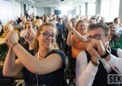Uczestnicy konferencji podczas wspólnych ćwiczeń wtrakcie przerwy, unoszą ręce dogóry. Napierwszym planie Alicja Długołęcka.