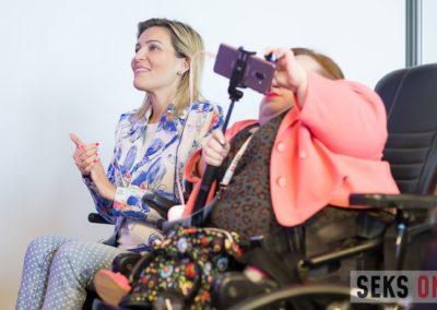 Dwie kobiety siedzą obok siebie - Agata Roczniak klaszcze, aBogumiła Siedlecka-Goślicka robi zdjęcie telefonem.
