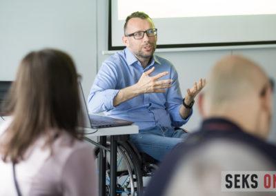 Tomasz Biduś, gestykuluje podczas swojego wykładu.