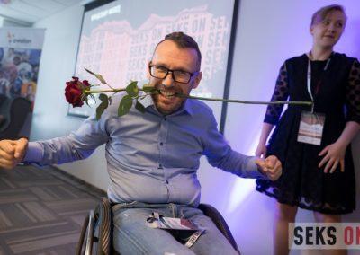 Tomasz Biduś trzymający różę wzębach.