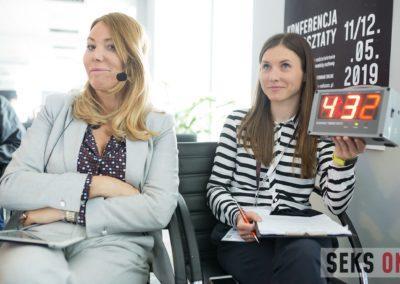Dwie kobiety siedzące obok siebie. Prowadząca konferencję - Agata Niemiec iwolontariuszka, trzymająca wręku licznik odmierzający czas wystąpienia.