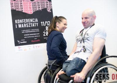 Mężczyzna ikobieta nawózkach mijają się wkorytarzu. Wtle plakat konferencji.