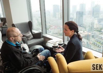 Uczestnicy konferencji wtrakcie rozmowy podczas przerwy kawowej. Kobieta siedząca nafotelu orazmężczyzna nawózku.