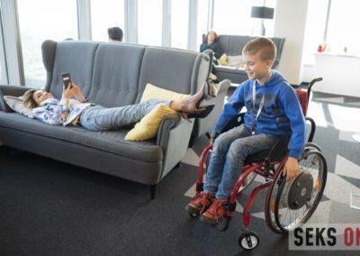 Agata Roczniak leży nakanapie ibawi się komórce. Obok niej jej syn siedzący najej wózku.