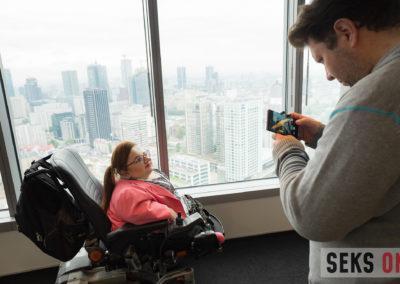 Mężczyzna robi zdjęcie telefonem Bogumile Siedleckej-Goślickiej. Kobieta siedzi nawózku elektrycznym.