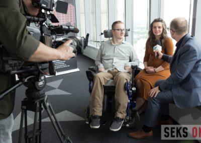 Redaktor przeprowadza wywiad zAnną iArturem Wachowiczami. Napierwszym planie kamerzysta.