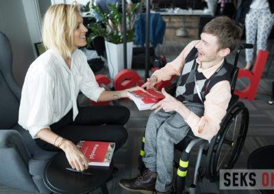 Ania Rubik rozmawia zuczestnikiem konferencji ipodaje mu książkę #sexedpl. Kobieta siedzi wfotelu, amężczyzna nawózku.