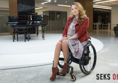 Monika Kuszyńska nawózku, pozująca wholu budynku.