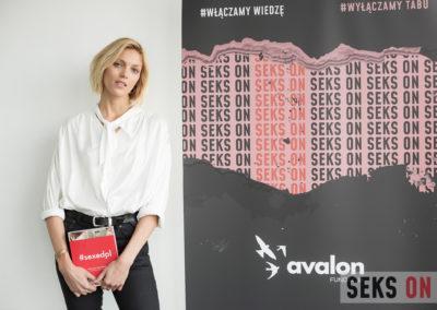 Anja Rubik stojąca obok plakatu konferencji Sekson. Trzyma książkę #sexedpl
