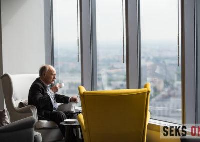Marek Cytatcki pijący kawę. Siedzi wfotelu ispogląda przezokno.