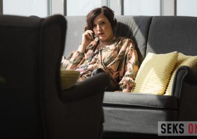 Katarzyna Hajduga siedzi nakanapie irozmawia przeztelefon.