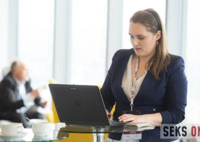 Organizatorka konferencji stoi przy stoliku kawowym ipracuje nalaptopie.