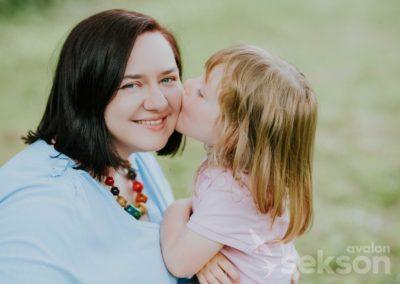 Małgosia iJulia. Małgosia jest zwrócona twarzą wobiektyw, uśmiecha się, Julia całuje ją wpoliczek.