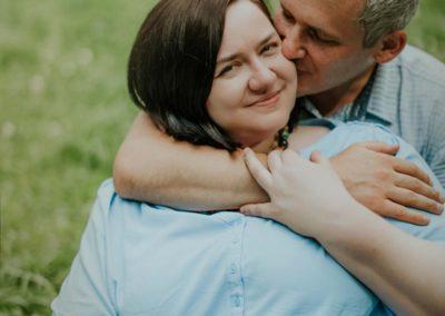 Widać Małgosię odpasa wgórę zanią siedzi Piotr, któryobejmuje jej szyję ramieniem icałuje ją wpoliczek, ma zamknięte oczy. Małgosia się lekko uśmiecha.