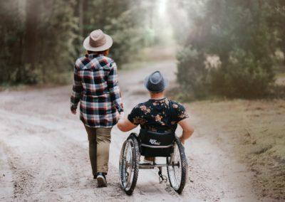 Magda zArturem są wlesie, Magda stoi obok Artura, którajest nawózku inwalidzkim, trzymają się zarękę.