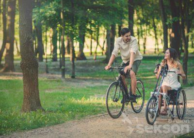 Karol zJulią narowerach jadą przezpark. Julia jedzie narowerze dostosowanym dojej wózka inwalidzkiego.