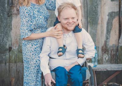 """Łukasz siedzi nawózku, ma nasobie białą koszulę. Najego ramionach """"nabarana"""" siedzi Adaś. Obok nich stoi Danusia wdługiej sukience wniebieskie kwiatki. Wszyscy się usmiechają. Zanimi nadrugim planie leży pies."""