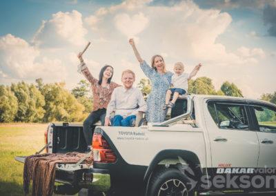Łukasz, Danusia zdziećmi napace terenowego samochodu. Kobiety iAdaś unoszą ręce dogóry. Pośrodku siedzi Łukasz. Wszyscy się uśmiechają. Wtle widać drzewa iniebo.
