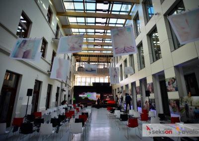 Zdjęcie sali konferencyjnej wtrakcie przygotowań dokonferencji. Sala wypełniona pustymi krzesłami, wtle obsługa konferencji.
