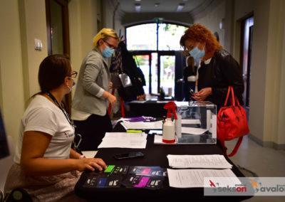 Punkt rejestracyjny, dwie organizatorki, jedna siedzi, druga stoi, przy punkcie stoi jedna zuczestniczek konferencji.