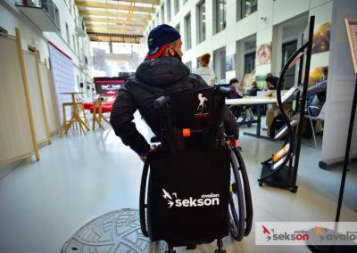 Zdjęcie zrobione odtyłu. Młody mężczyzna nawózku inwalidzkim, uczestnik konferencji. Narączkach wózka wisi torba zlogiem projektu Sekson.