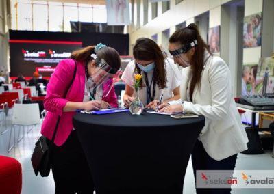 Trzy organizatorki stoją przy stoliku, wypełniają dokumenty