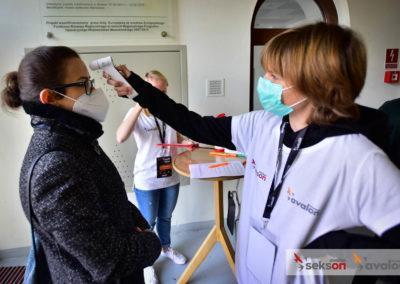 Wolontariuszka wmaseczce mierzy temperaturę uczestniczce konferencji wpunkcie rejestracyjnym.
