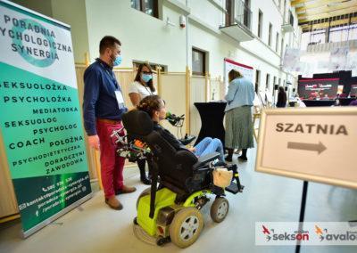 Wejście nasalę konferencyjną, polewej stronie baner, przy nim uczestnicy konferencji: kobieta nawózku elektrycznym imężczyzna. Obok nich jedna zorganizatorek konferencji.
