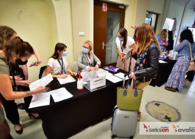 Punkt rejestracyjny. Przy stole zdokumentami siedzą organizatorki konferencji. Obok stoi jedna zuczestniczek konferencji, odbiera pakiet.