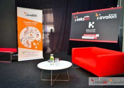 Wnętrze zaaranżowane namini studio. Natle czarnej, materiałowej ścianki materiały promocyjne Fundacji Avalon. Poprawej stronie czerwona sofa, naśrodku niski, biały stolik nametalowych nóżkach. Wprawym dolnym rogu fotografii logotypy Fundacji Avalon iprojektu Sekson.