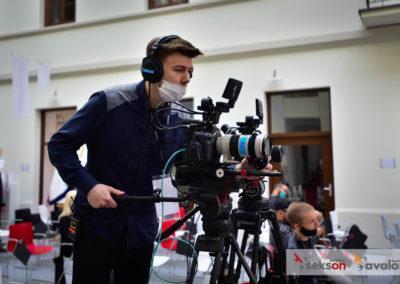 Kamerzysta, wsłuchawkach imaseczce, operuje kamerą.