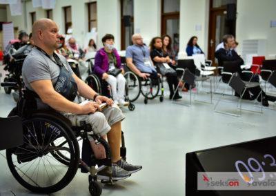 Uczestnicy konferencji, napierwszym planie mężczyzna nawózku inwalidzkim, jeden zuczestników.