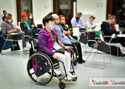 Grupa uczestników konferencji, napierwszym planie młoda kobieta nawózku inwalidzkim.