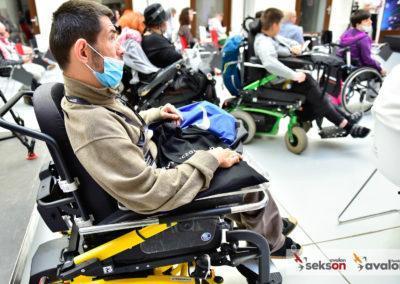 Zdjęcie zrobione zboku, napierwszym planie jeden zuczestników konferencji - mężczyzna nawózku inwalidzkim, wmaseczce. Wtle pozostali uczestnicy.