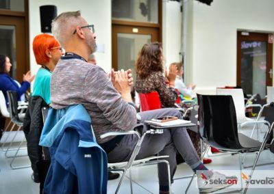 Zdjęcie zrobione zboku, uczestnicy konferencji nakrzesłach, klaszczą.