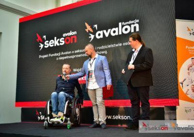 Sebastian Luty, Łukasz Wielgosz iKrzysztof Dobies nascenie, zanimi duży ekran zlogo projektu Sekson ilogo Fundacji Avalon. Łukasz trzyma mikrofon Sebastianowi.