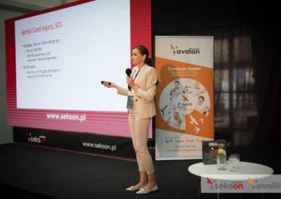 Monika Łukasiewicz prezentuje swój wykład nascenie. Obok niej duży ekran zprezentacją.