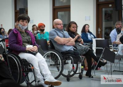 Grupa siedzących uczestników konferencji.