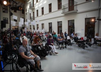 Sala, wktórejodbywa się konferencja, nasali uczestnicy konferencji, część siedząca nawózkach inwalidzkich, część osób siedzi nakrzesłach.