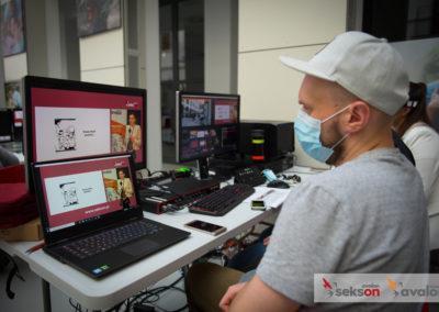 Mężczyzna wmaseczce, jeden zorganizatorów konferencji, siedzi przedmonitorem komputera, kontroluje transmisje konferencji.