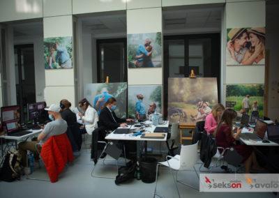Organizatorzy konferencji przy biurkach, pracują przy laptopach. Wtle naścianie wiszą prace fotograficzne projektu Pełnosprawni wmiłości.