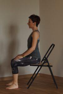Kobieta siedzi naskraju krzesła, jest wyprostowana.